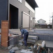 エントランスはシンプルモダンなコンクリート平板で階段アプローチを作成します。門柱はイタウバで制作。