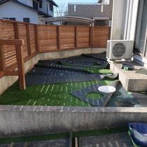 雑草防止シートを敷き詰めてから人工芝を細断、配置します。これから連結部分を接着工します。
