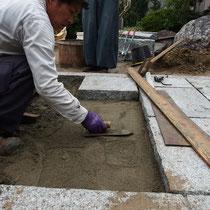 厚みが凸凹の底面を持つ重い敷石、下地と何度も照らし合せて敷設します。