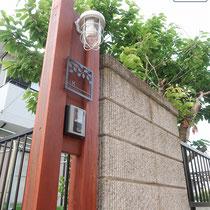 ハードウッドに赤褐色の塗装を施した門柱、自動車の出入りに邪魔にならないようスリムに仕上げ、マリンランプと表札を取付ます。