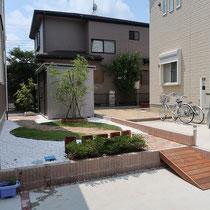 庭の奥に通じるレンガ舗装を中心に、低い枕木と物置前に植えるシマトネリコ、突き当りには縦格子フェンスがみえるお庭になりました。