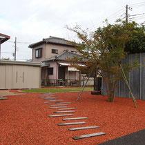 駐車場からみた風景、既存のコンクリート枕木を利用し奥行き感あるお庭に続きます。隣地の殺風景な壁の前にはアイストップとなるモミジを植えます。