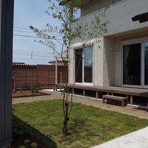 お部屋の前に広がる芝生のお庭、その奥に見えるのは擬木枕木の家庭菜園とウッドフェンスです。