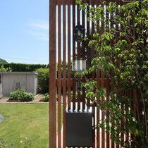 縦格子の背の高いスクリーンフェンス。ヤマボウシのさらさらした植物と、繊細なガラス表札がよく合います。