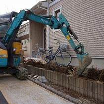 お庭の掘削作業にあわせ、道路側のアベリアの根っこを重機で掘りあげます。
