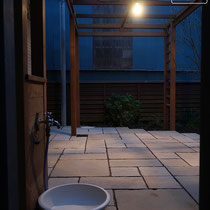 壁面に取り付けた屋外スイッチでライトアップ、幻想的な石畳のテラスが出来ました。