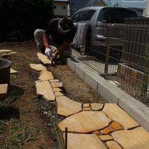 芝生と花壇の見切りに乱形石を使用。大小混ぜて貼る仕上には職人さんの細やかな個性が表れます。