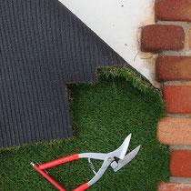 凹凸のあるレンガのふちに合わせ、人工芝をカットします。縫い目を見ながら綺麗に収まるようにしました。