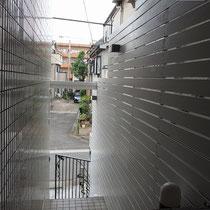 完成写真。目隠しを兼ねつつ建物を引き立てるシンプルなホワイト塗装のウッドフェンスが出来ました。