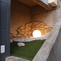 別の場所の坪庭。階段脇の小さなスペースですが、コンクリート壁の無機質な印象を、コッツウォルズ石と人工芝、LED球体で明るい印象に変えました。