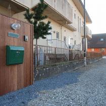 表札等をまとめた木製門塀は大きく目立つような仕上がりで、矢印形状の表札でユニークに来客をお招きします。