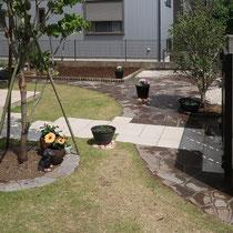 アプローチタイルを境に左右に分かれた庭、石畳でつながりを感じる景観になりました。