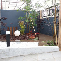 既存タイルの延長線に300角のポルフィード石を使った深い色合い、建物に合わせた落ち着いた外壁仕上で奥行あるお庭になりました。
