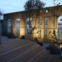 待合室から眺められるウッドデッキの中庭、既存のRC壁に間接照明をあてて植物のシルエットが浮かび上がる演出です。