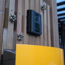 黄色いポストが印象的!インターホン周りにはプルメリアの真鍮飾りを取付しました。