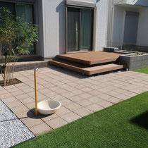 完成したお庭、人工芝とウッドデッキの間には、コンクリートの平板テラスを作成。立水栓がアクセントになります。