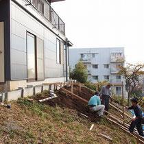 デッキ工事着工時、結構な傾斜地です。まずは大工さんに高低差の確認をしてもらいます。