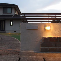 真鍮ライトと自然石、ウッド調フェンスと塗壁の素材感が溶け合い、ナチュラルで優しい上質感があります。
