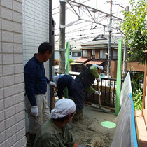 施工中、ポンプ車を使って一気にコンクリートを流し込みます。建物やフェンス等周囲を養生しながらの作業。