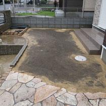 人工芝の下地、土壌を整地後に川砂で均し、外周の際には固まる土で雑草対策をかねつつ、最後に雑草防止シートを敷きこみます。
