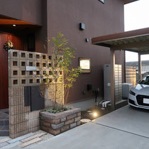 玄関扉の前には目線をとめるスクリーンブロックの門塀。宅配ポストと一般ポストを並べ、砂岩石の花壇にシマトネリコを植えます。