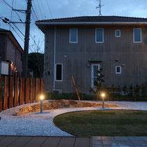 夕方の風景。ガーデンライトは三日月の石積を照らしだし、砂利と芝生のコントラストを演出してくれます。