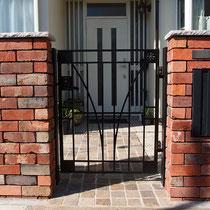 ポルフィード石畳とレンガ門塀、笠木には割肌仕上げの桜ミカゲ。アルミ鋳物で格調あるエントランスに仕上がりました。
