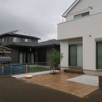 デッキを囲うブロック花壇、コンクリート平板のテラスが完成。人工芝の下地には川砂を敷き込みます。