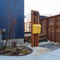 門柱周りは枕木風アプローチと植栽。施主支給されたイエローのポストもセンスいいですね!