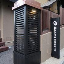 イタウバで作成した門柱に銅板の屋根、オイルステイン塗装で黒く塗り表札灯も設置しました。