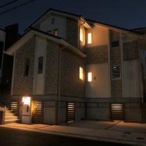 夜のライトアップ写真。さりげなく演出される灯りがフェンスの隙間からグラデーションのように見えます。