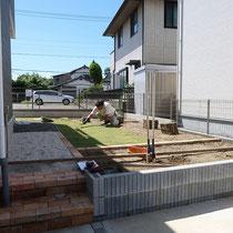 庭の入口としてレンガ階段、芝生と花壇を見切るレンガ縁石を施工。デッキを作成する予定の場所には砂利敷きを施します。