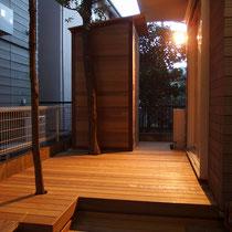 既存の植木がデッキから伸びた、ライトアップで一層雰囲気が良いウッドデッキと物置です。