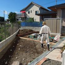手前は自転車置場となるコンクリート舗装を予定。奥にはレンガ花壇を作成中です。