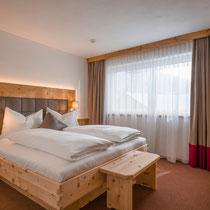 Ein gemütliches Bett mit einem Zirbenrahmen kombiniert mit echtem Altholz. Das gepolsterte Kopfhaupft sorgt für Gemütlichkeit und entspannte Leseabende.