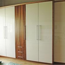 Elegantes Schrankdesign aus europäischem Nußholz und weißen Hochglanz-Fronten. Das Innenleben beinhaltet eine Menge raffinierter Details.