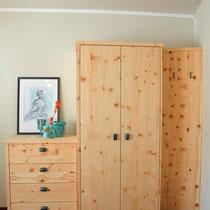 Ansicht vom Bett aus. Ein schlichter Schlafzimmerschrank in Zirbe mit Ladenkommode und einem offenen Garderobenteil.