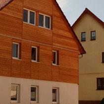 Die alte Fachwerkfassade wurde mit Holzfaser gedämmt und mit naturbelassenem Lärchenholz verkleidet.