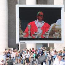 Papst Franziskus bei der Messe am Feiertag - auf Großbildleinwand auf den Petersplatz übertragen