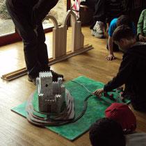 Atelier château : création d'arcs avec la maquette (au fond : arcs en plein-cintre et brisé), puis reconstitution d'un site castral avec donjon, remparts, routes, village... pour acquisition du vocabulaire