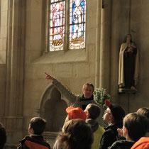 La visite porte ensuite sur les particularités de l'église : ici, l'ensemble de vitraux le plus ancien du Limousin, à la collégiale d'Eymoutiers, observés avec des jumelles !