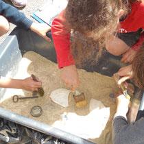 Atelier archéologie : fouille de bacs avec mobilier archéologique. 4 bacs différents : Préhistoire (2 bacs), Antiquité et début XXe siècle (ici)