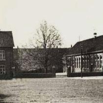 De Sint Bavoschool met paarden , in de tijd dat er nog gras groeide op het Markt/kermisplein waar periodiek paardenmarkten werden gehouden. Aan de linkerkant hebben nog lang de palen met stangen gestaan waar de paarden aan werden vastgelegd