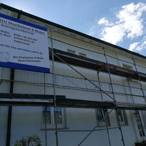 Fassadensanierung mit neuer Farbe und neuem Lack mitten in der Renovieung.