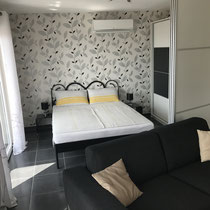 Der Schiebetür zum Schlafzimmer kann weit aufgemacht werden, so dass der Wohnbereich offen gestaltet bleibt