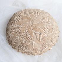 Rundes Kissen gestrickt mit Füllung in beige