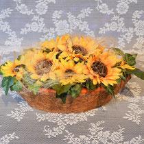 Herbstgesteck mit Sonnenblumen im Kokosschiff.