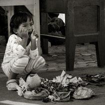 Bali / Indonesien: Ein kleines Mädchen sitzt vor landestypischen Opfergaben