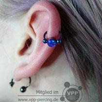 Helix Piercing mit dem Titanring und dem Klemmelement mit synthetischem opalstein. Anodisiert Blau-Lila. Stärke: 1,6mm.