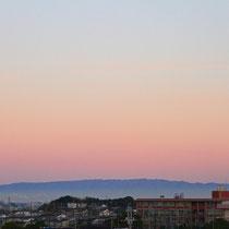 秋の朝、ウチの廊下側から北西に見える六甲山。   上空がピンク色に染まっていました。